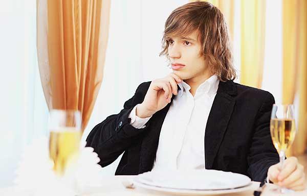 高級レストランでディナーをとる男