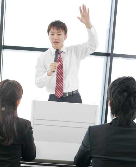 演壇に立って手を挙げている男性