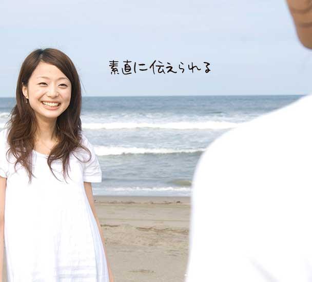 浜辺で男性に笑顔を向けて立つ女子