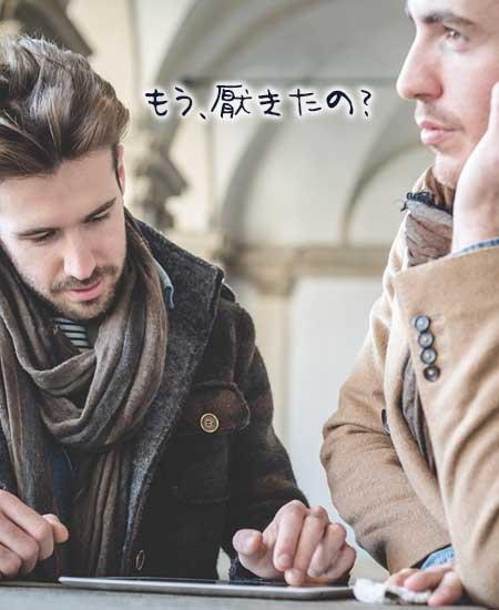 タブレットを見る男性とそっぽを向く男性
