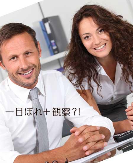 職場で並んで笑顔のカップル