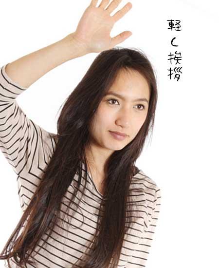 片手を上げて挨拶する女性