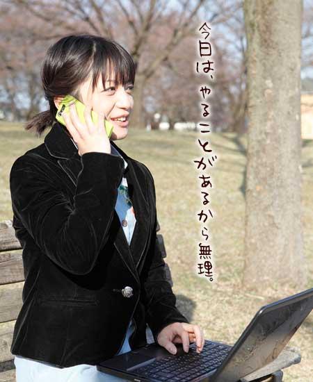 公園のベンチでノートパソコンを操作しながら電話を受ける女性
