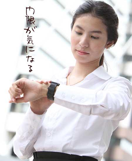 外で腕時計を見る女性