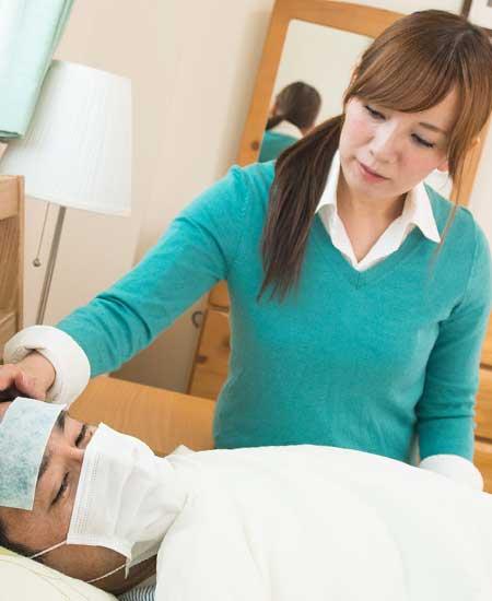 風邪で寝込む男性を看病する女性