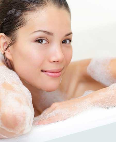 浴槽で体を洗う女性