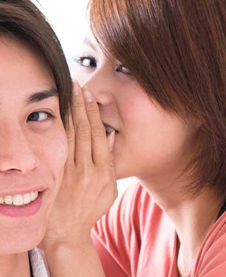 男性の耳元で囁く女性