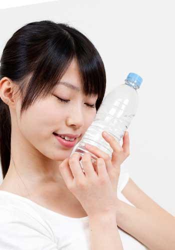 ペットボトルの水を持った女性