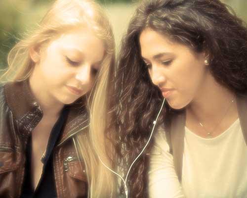 イヤホンで一緒に音楽を聞く女性二人