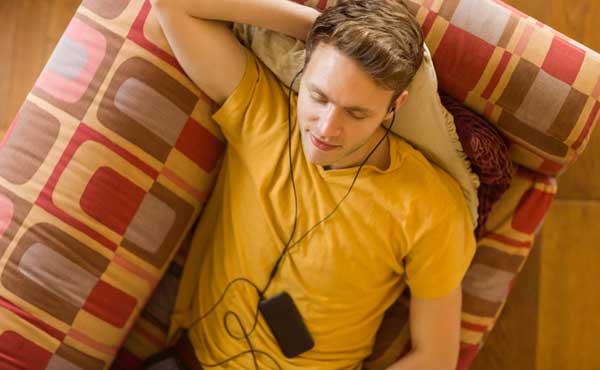 スマホで音楽を聴きながら寝る男性