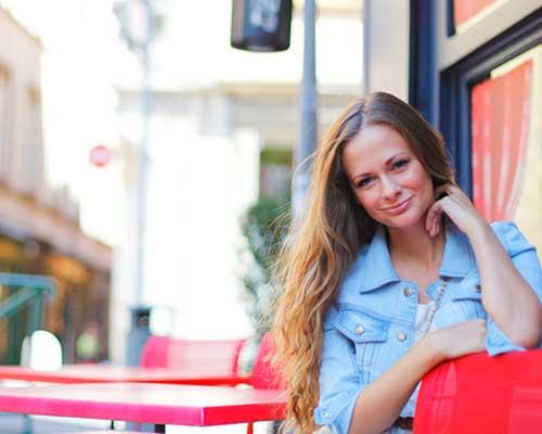外のカフェの座席に座る女性