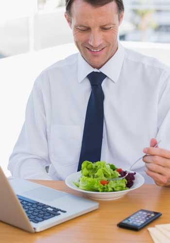 PCとスマホの前でサラダを食べる男性