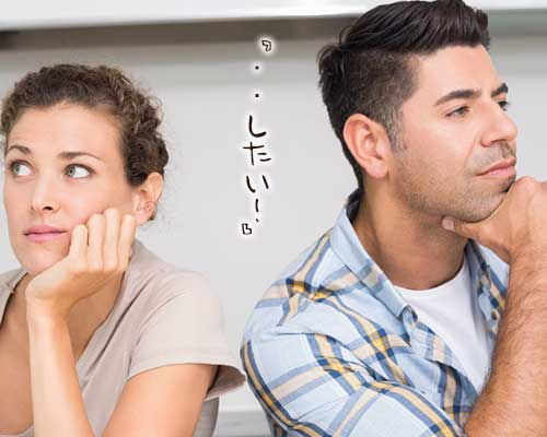互いに顔をそむけて座るカップル