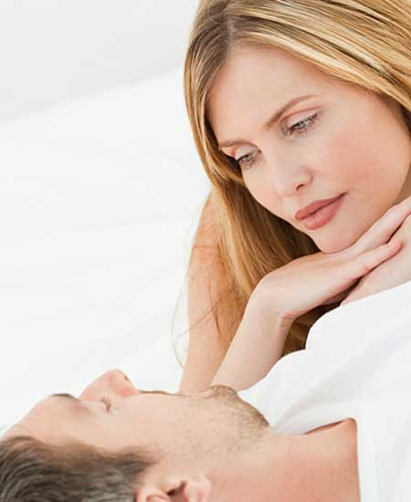 横になる彼の胸に顔をのせて見つめる女性