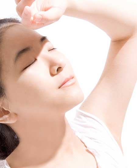 手を挙げて紫外線から顔を守る女性