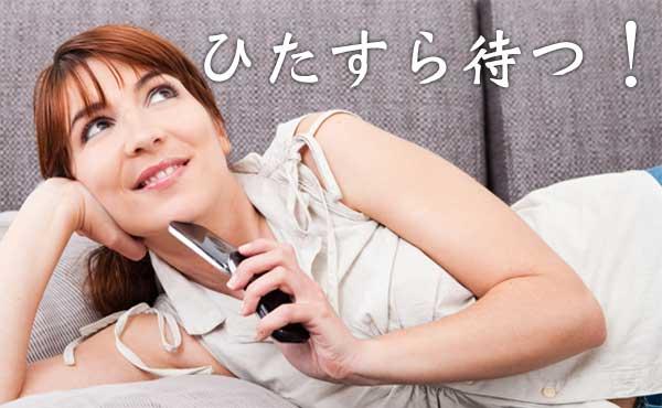 ケータイをもって横になる女性