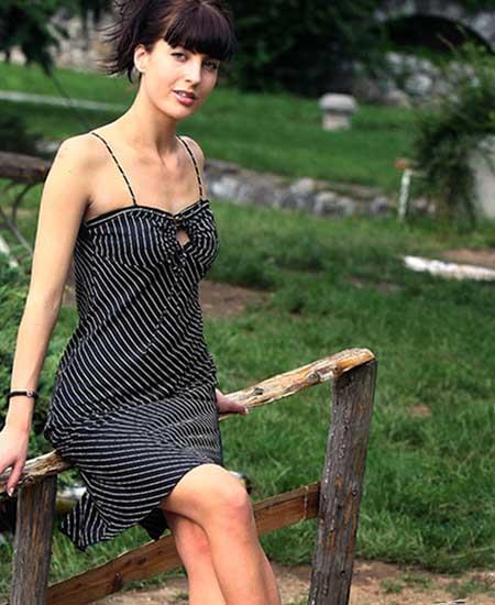公園の柵に腰掛ける女性