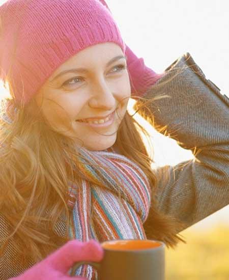 帽子とマフラーしてコーヒー飲む女性