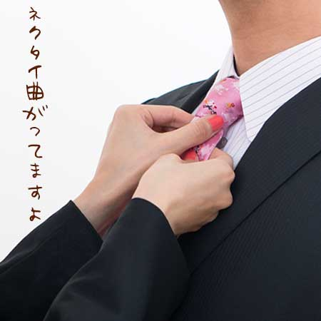 ネクタイを直してあげる女性