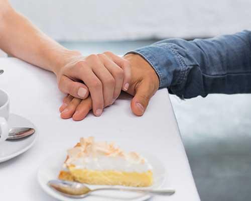 食卓で彼の手を触る女性