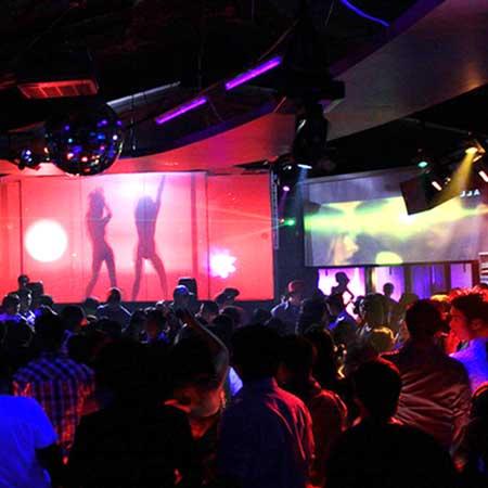 クラブの派手な照明と踊る男女