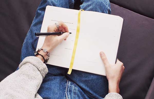 ノートを書く女性