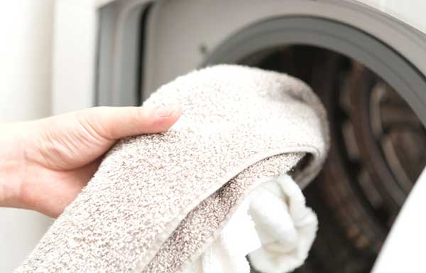 洗濯機にタオルを入れる