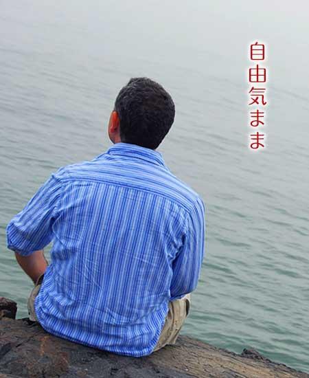 海に向かって一人で座っている男性