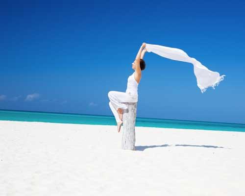 砂浜でスカーフを風になびかせている女性