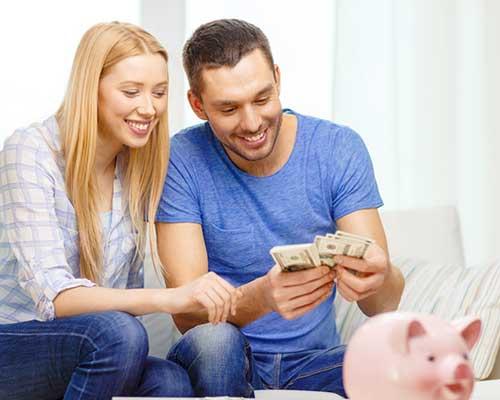 貯金箱を前に紙幣を数えるカップル