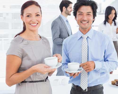 コーヒーカップを持って並んで立つ男女