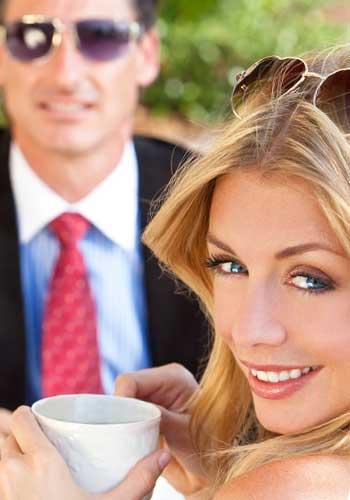 サングラスの男性とお茶をする女性