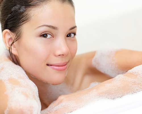 浴槽の縁に腕をかけて微笑む女性