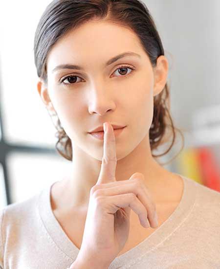唇に人差し指を当てる女性