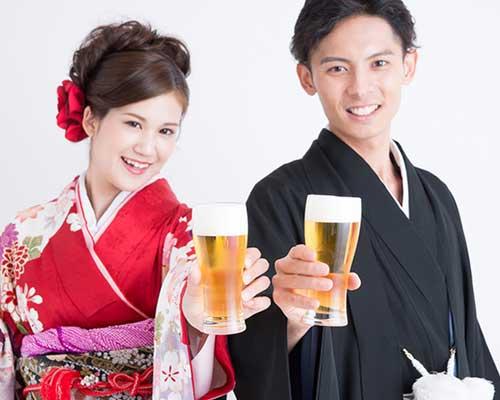 ビールで乾杯する和服姿の男女