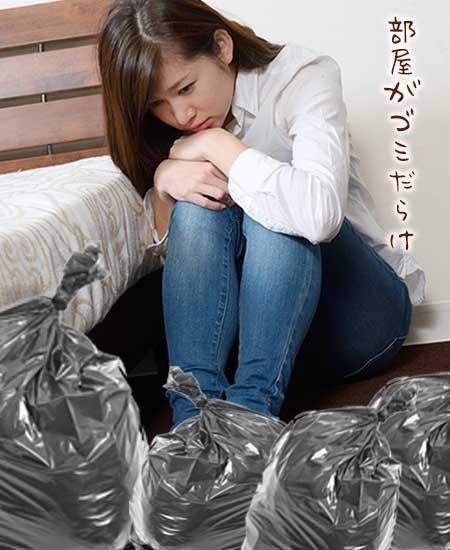 部屋でゴミ袋に埋もれてうずくまる女性