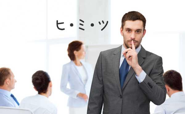 職場で内緒のポーズをする男性