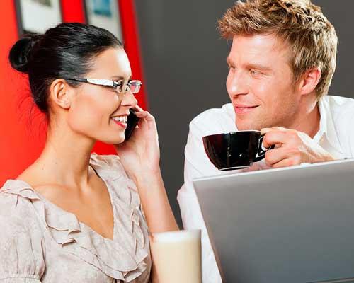 ノートパソコンを見ながらランチをとる男女