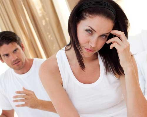 寝室で不満げな彼と首をかしげる女性