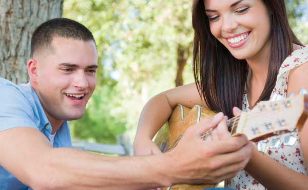ギターを弾く女性と教える男性