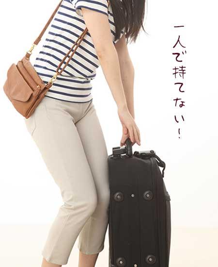 キャリーバッグを重そうに持つ女性