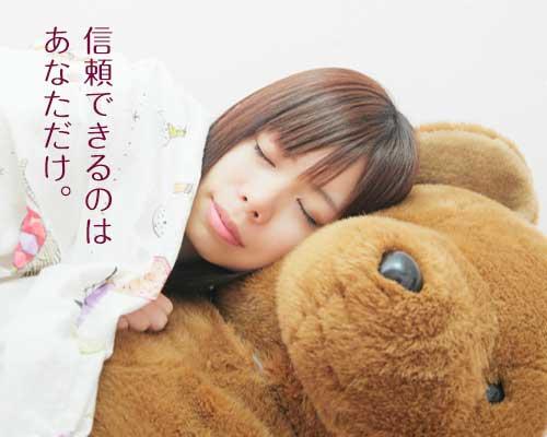 ぬいぐるみのクマと眠る女性