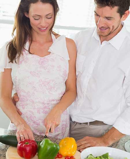 彼の傍らで料理する女性