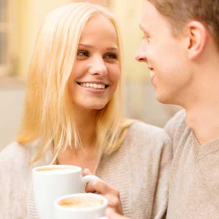 コーヒーを飲みながら見詰め合うカップル