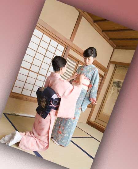 若い女性に着物の着付けをする女性