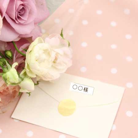 花の脇に置かれた名前付箋つきの封筒