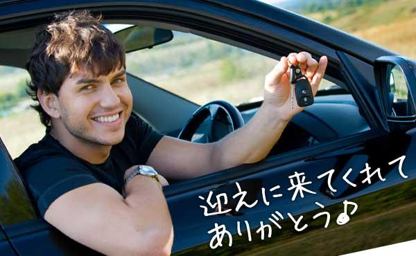 車内から鍵を見せる男性