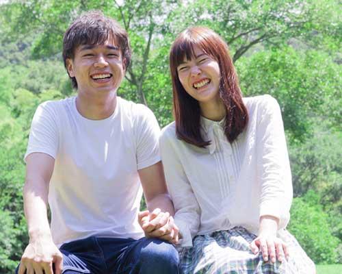 二人で笑いながら手を結ぶカップル