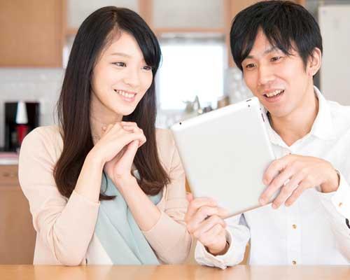 二人でタブレットを見るカップル