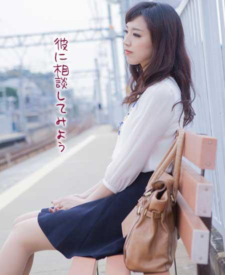 電車ホームで待つ女性